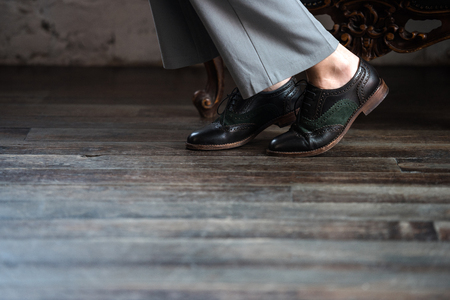 low section of woman in stylish leather shoes and grey trousers Stock Photo