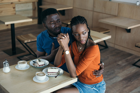 insulted african american woman with boyfriend sitting at table in cafe