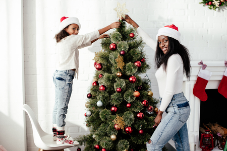 African American mother and daughter in Santa Claus hats decorating Christmas tree together at home