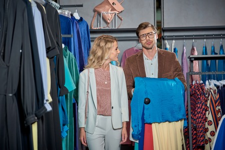 Young couple choosing stylish clothes in showroom Foto de archivo - 111107392