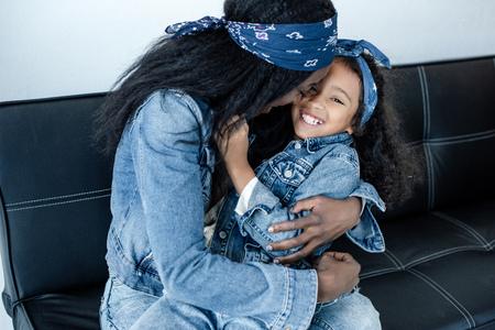 African American woman and cheerful daughter having fun on sofa at home 版權商用圖片