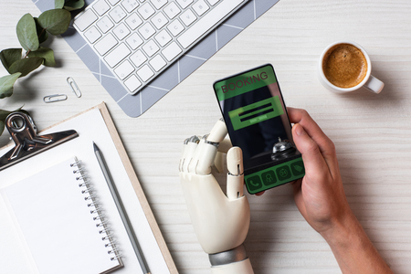 Partial view of businessman with prosthesis arm using smartphone at table with coffee cup in office Stock Photo