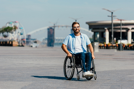 Cheerful handsome man in sunglasses using wheelchair on street