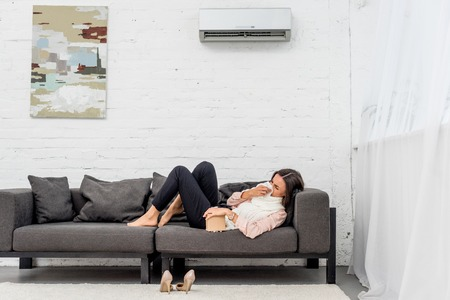 Side view of sick young woman lying on couch at home