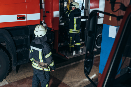 Partial view of firefighters in fireproof uniform and helmets at fire station Stockfoto