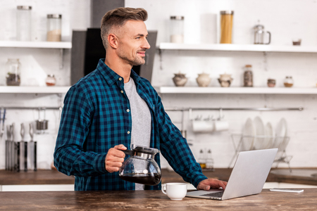 Handsome smiling man holding coffee pot and using laptop at home