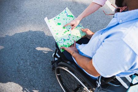 Cropped image of boyfriend in wheelchair holding map and girlfriend pointing on location on street Stock Photo