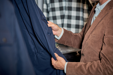 Cropped shot of man choosing clothes while shopping in boutique Foto de archivo - 111165387
