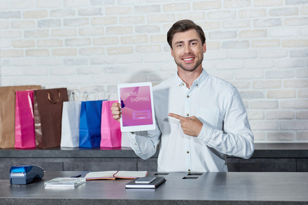 Handsome young salesman pointing at digital tablet with online shopping application and smiling at camera in store Stockfoto
