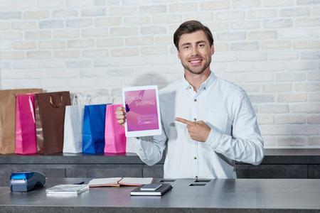Vendedor joven guapo apuntando a la tableta digital con la aplicación de compras en línea y sonriendo a la cámara en la tienda