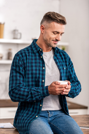 Handsome smiling man in checkered shirt holding cup of coffee at home 版權商用圖片 - 111165665