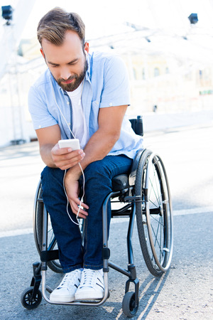 Handsome man in wheelchair listening to music and using smartphone on street