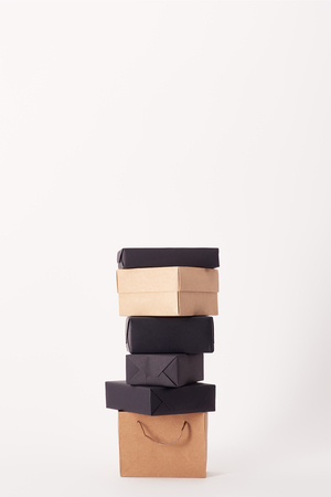 Shopping bag and stacked boxes on white surface, black Friday concept Stok Fotoğraf