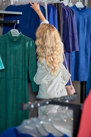 Beautiful young woman looking at stylish clothes while shopping in boutique Foto de archivo - 111165573