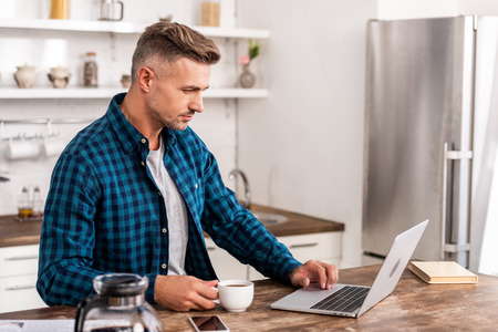 Handsome man in checkered shirt holding cup of coffee and using laptop at home