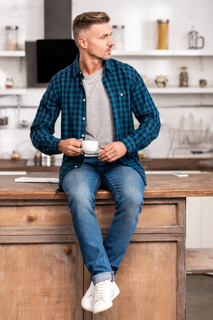 Handsome man in checkered shirt holding cup of coffee and looking away at home
