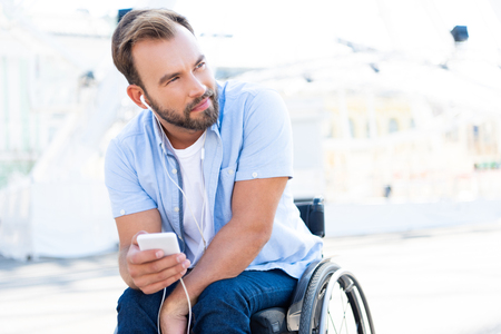 Handsome man in wheelchair listening to music with smartphone on street and looking away Stock Photo
