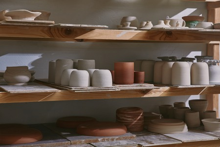 Ceramic bowls and dishes on wooden shelves at pottery studio Reklamní fotografie - 111165706