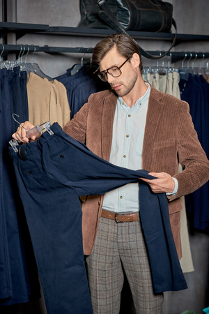 Handsome man in eyeglasses holding hanger with stylish pants in boutique Foto de archivo - 111166217