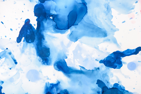 Blue splashes of alcohol ink on white as abstract backdrop