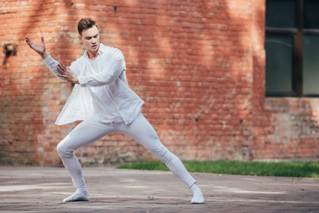 Young male ballet dancer in white clothes dancing on urban street Stock Photo