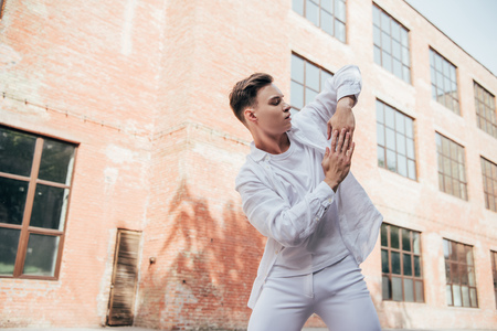 Handsome young man in white clothes dancing on street Foto de archivo - 111166791