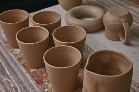 Selective focus of ceramic pots at table in pottery studio