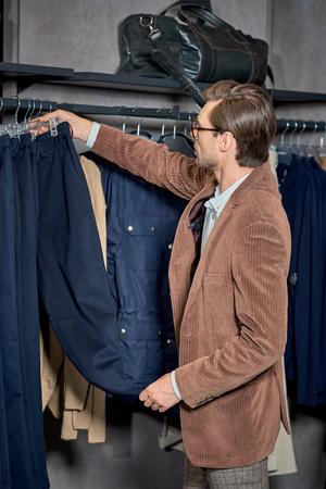 Handsome stylish man in eyeglasses choosing fashionable clothes in shop Foto de archivo - 111166673