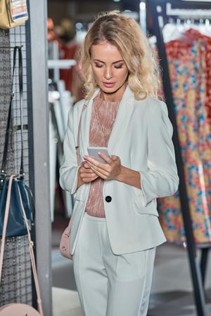 Beautiful young woman using smartphone while shopping in fashion store Foto de archivo - 111166955