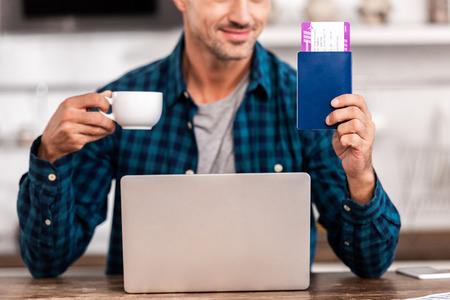 Cropped shot of smiling man holding cup of coffee and passport with boarding pass while using laptop at home Stock Photo