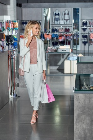 Smiling young woman with paper bags talking by smartphone and looking away while shopping in store Foto de archivo - 111167517