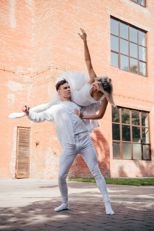 Young ballet dancers in white clothes dancing on city street Stock Photo