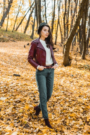Fashionable young woman in beret and leather jacket walking in autumnal park Banco de Imagens