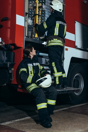 Female firefighter in protective uniform looking at colleague checking equipment in truck at fire department