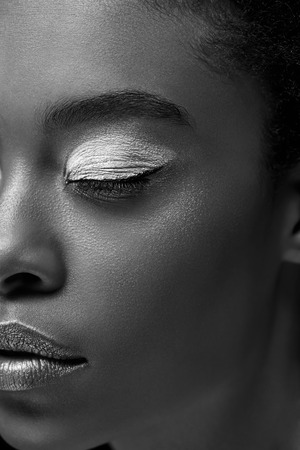 Black and white photo of African American woman with eye closed