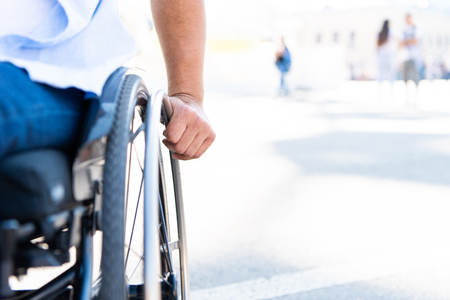 Cropped image of disabled man using wheelchair on street Stock Photo