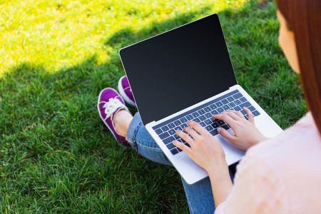 Cropped image of freelancer using laptop with blank screen in park Archivio Fotografico