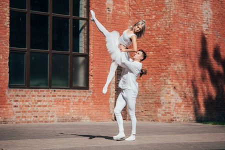 Beautiful young couple of ballet dancers performing on urban city street Stock Photo