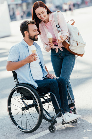 Girlfriend with ice cream showing something on smartphone to handsome boyfriend in wheelchair on street Stock Photo