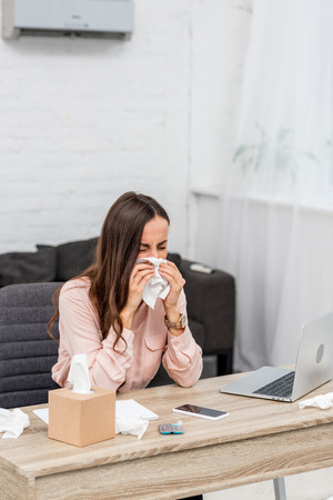 Ill young businesswoman blowing nose with paper napkin at workplace