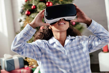 African American child in pajamas using virtual reality headset at home, Christmas concept