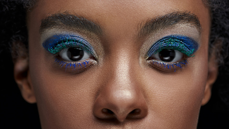 Cropped shot of African American woman with blue eye shadows looking at camera isolated on black background