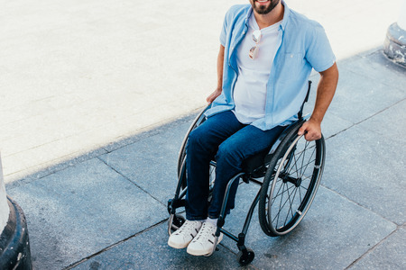 Cropped image of man using wheelchair on street Stock Photo
