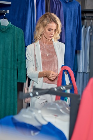 Attractive young woman looking at stylish clothes while shopping in boutique Foto de archivo - 111170728