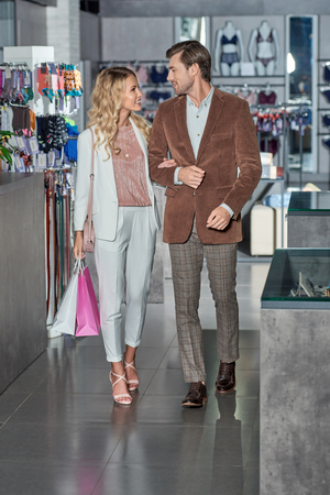 Stylish couple with shopping bags smiling each other in store Foto de archivo - 111170732