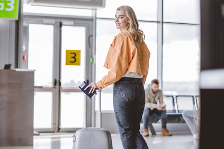 Girl with passport, boarding pass and suitcase smiling at camera in airport Stock Photo