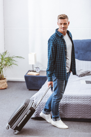 Smiling adult male traveler carrying wheeled bag at home Stock Photo