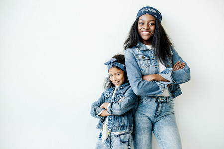 Stylish African American mother and daughter in similar clothing posing at wall at home 스톡 콘텐츠