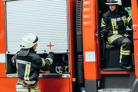 Firefighters in protective uniform and helmets at fire truck on street