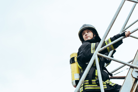 female firefighter in protective uniform and helmet with fire extinguisher on back standing on ladder with blue sky on background Stock Photo